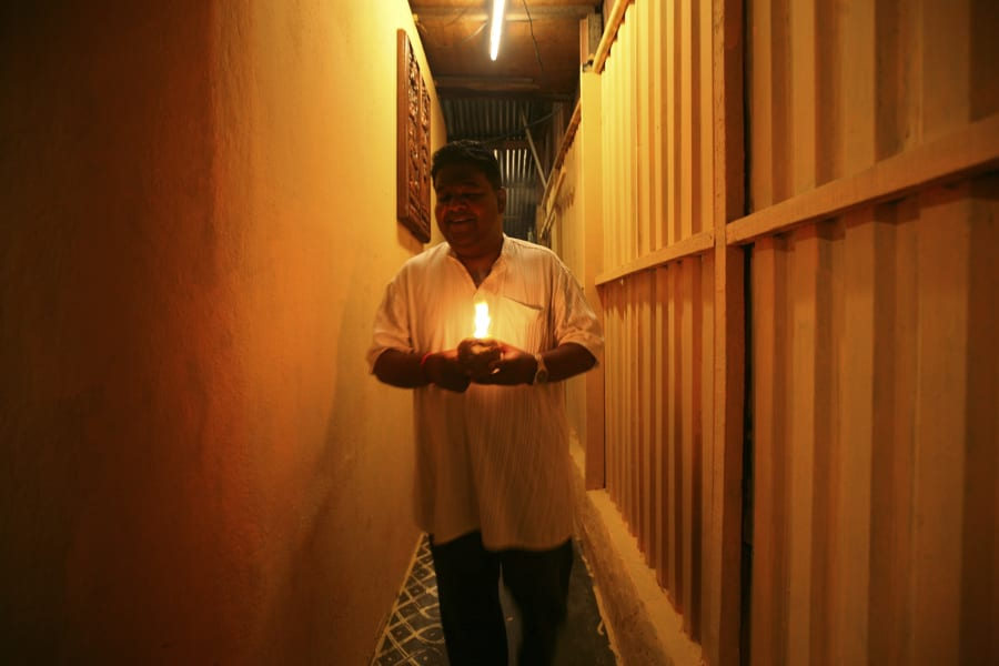 A Hindu man holds an oil lamp while offering prayers ahead of Diwali celebrations in Kuala