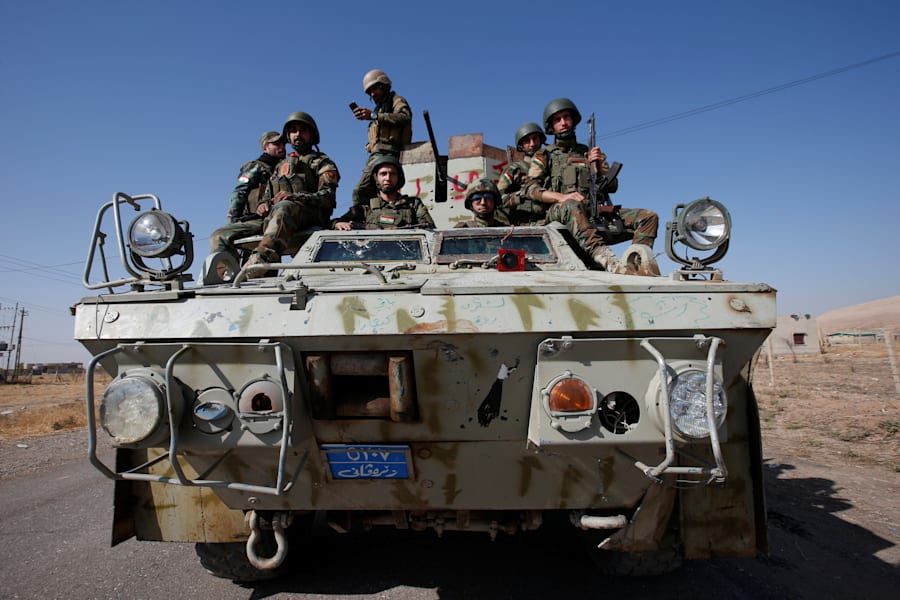 Syrian Kurdish fighters ride a military vehicle in the town of Bashiqa, after it was recaptured from...