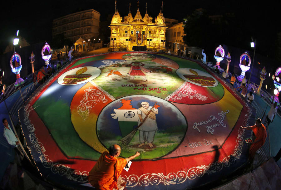 Hindu priests put the finishing touches to a rangoli artwork in the western Indian city of