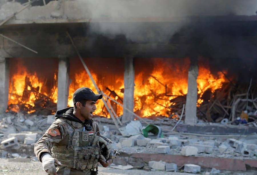 An Iraqi special forces soldier shouts in front of a burning house after an Islamic State suicide car...