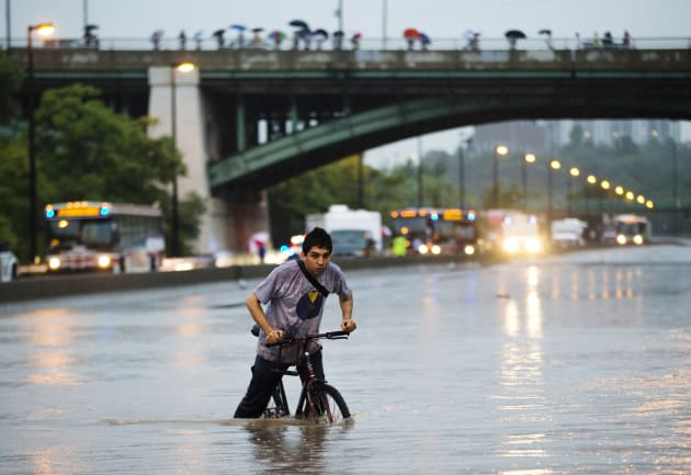 A man rides his bicycle during a flood on the Don Valley Parkway, a major highway, during a heavy rainstorm...