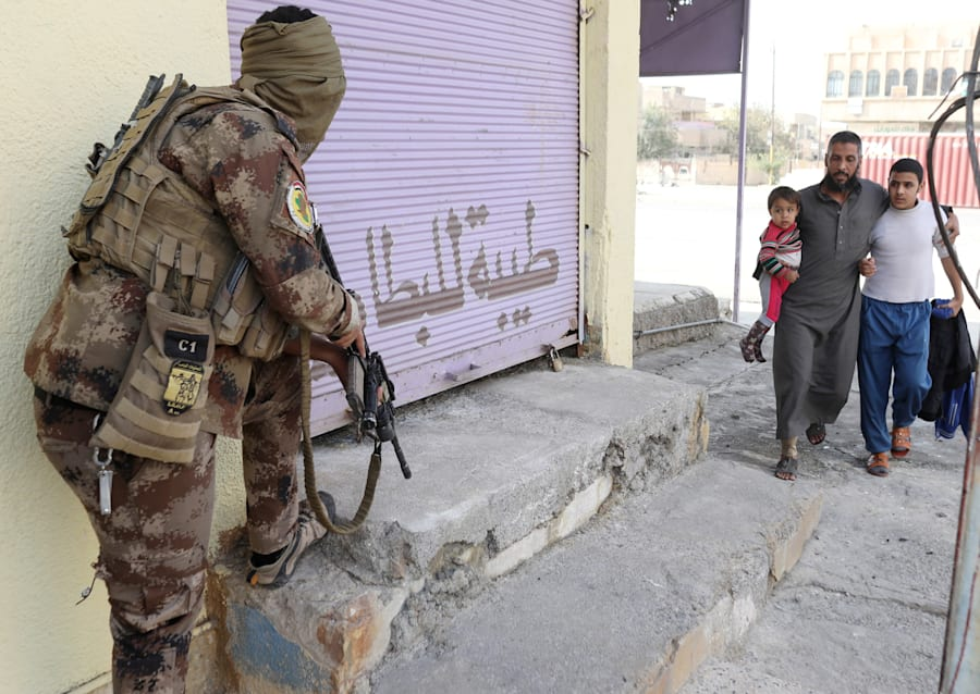 A man carries his child as he crosses from an Islamic State-controlled part of Mosul into an Iraqi-controlled...