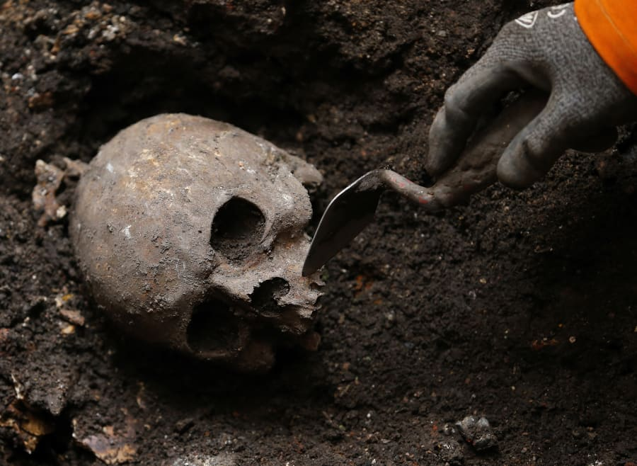 An archaeologist digs out skeletons from the site of the graveyard of the Bethlehem, or Bedlam, hospital...