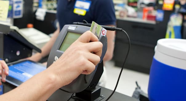 Female consumer uses, swipes credit card to make purchases at Wal-Mart Supercenter store in San Marcos, Texas