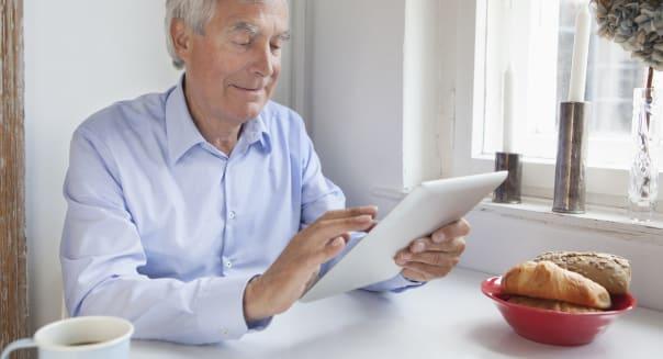Senior man using digital tablet at breakfast table