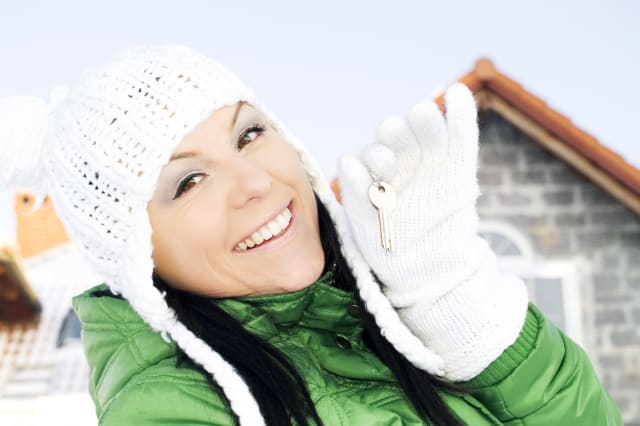 woman in winter clothes holding keys to the house