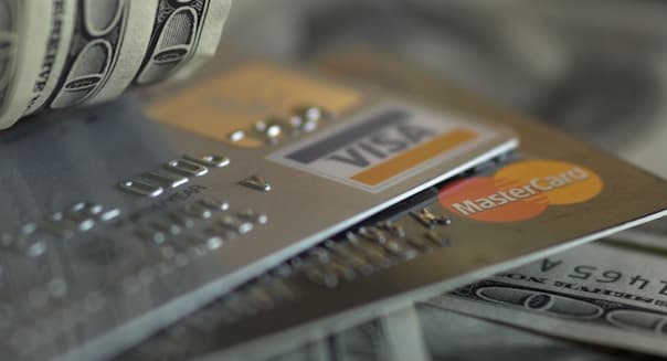 AN6WF9 credit card in the middle of US dollar notes. Image shot 2005. finance; money; USD; currency; dollars; credit; cards; mon