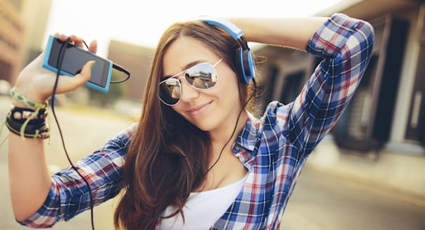 Cheerful teen dancing and moving along with music on her smart phone and headphones
