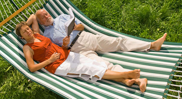 Senior couple lying in a hammock, woman listening to music, man reading a book