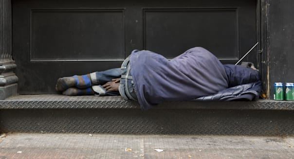 Homeless man sleeps on a building ledge in Manhattan.