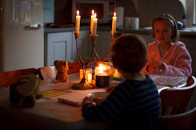 Image shows a young boy and girl sitting at the table eating breakfast. The room is lit by candles because there has been a powe