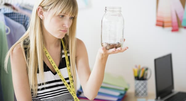 Woman holding empty savings jar