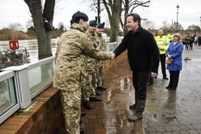 Prime Minister David Cameron chats with soldiers from the Royal Irish Regiment in Upton-Upon-Severn, where he is meeting local people and members of the military to discuss flooding measures and work in the community. PRESS ASSOCIATION Photo. Picture date: Monday February 17, 2014. See PA story WEATHER Floods. Photo credit should read: Ben Birchall/PA Wire