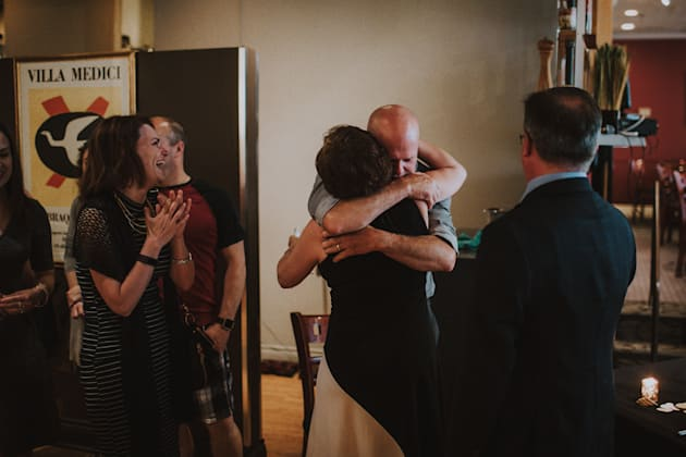 Eric, the father of the bride, sharing a hug with Jackie, the mother of the groom, as Karen, the stepmother...