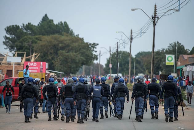 South African riot police deploy in Coligny following clashes that erupted after a court bailed two men...