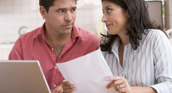 Couple in kitchen with paperwork using laptop look