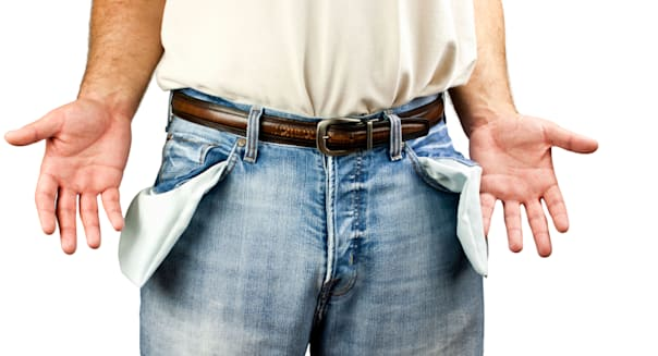 Young unemployed man dressed in blue denim jeans showing empty pockets isolated on white background with copy space.