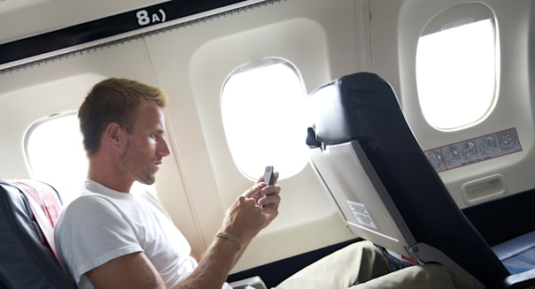 Guy sits browsing his smartphone as he sits in a window seat in a small plane