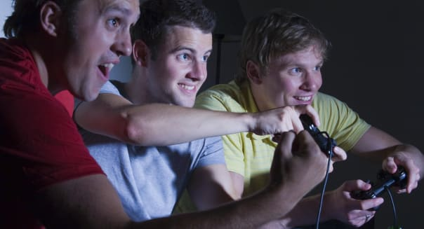 Three men playing a games console