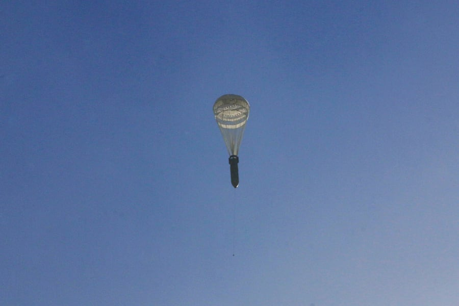 A missile hangs on a parachute while falling over the rebel-held besieged al-Qaterji neighbourhood of...