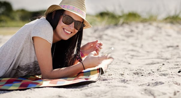 Portrait of happy woman holding mobile phone while lying on picnic blanket