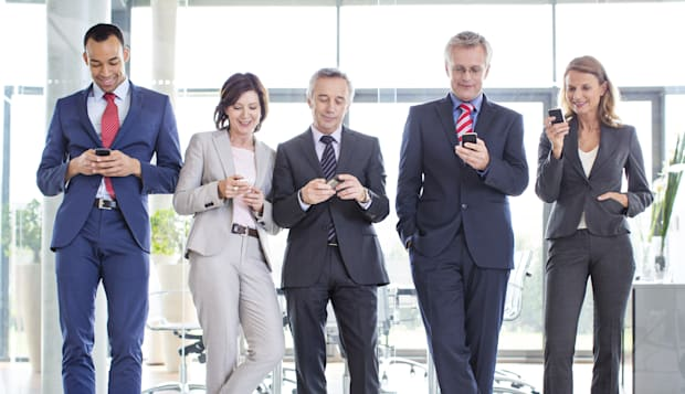 Business partners texting on their phones