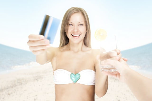 attractive young woman on the beach , paying for a cocktail with credit card
