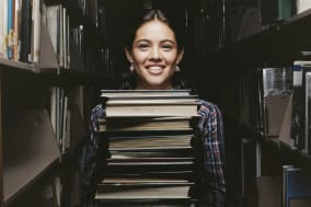 Secondary School Girl Stands Between Bookshelves in a Library Holding a Large Pile of Books