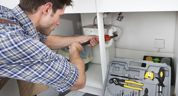 Plumber Fixing Sink In Kitchen