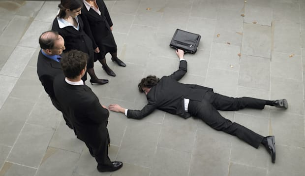 Business people looking down at man lying on pavement, elevated view