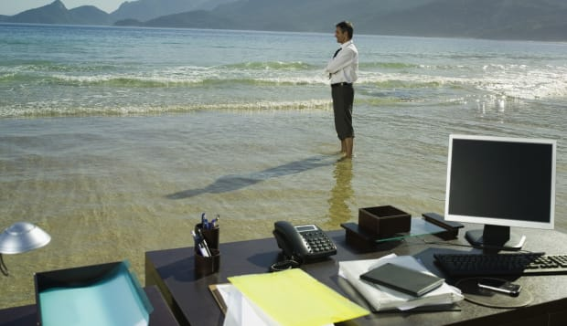 Businessman on beach with office desk, smiling