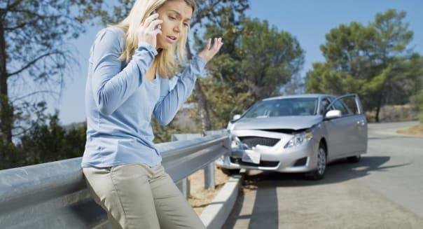 Frustrated woman using cell phone next to car wrecked on guardrail