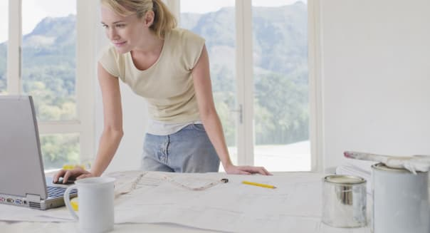Woman using laptop at table with blueprints and paint