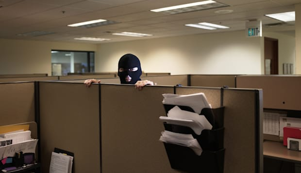 Office worker wearing balaclava, standing behind office partition