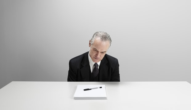 Worried businessman looking at blank paper and pen