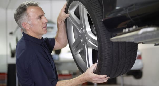 Mechanic changing tire in auto repair shop
