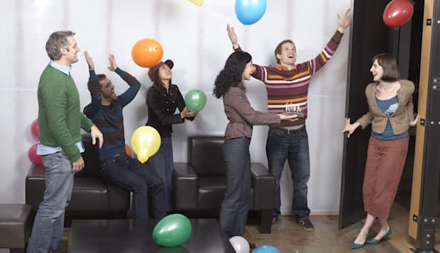 Co-workers at surprise birthday party, smiling