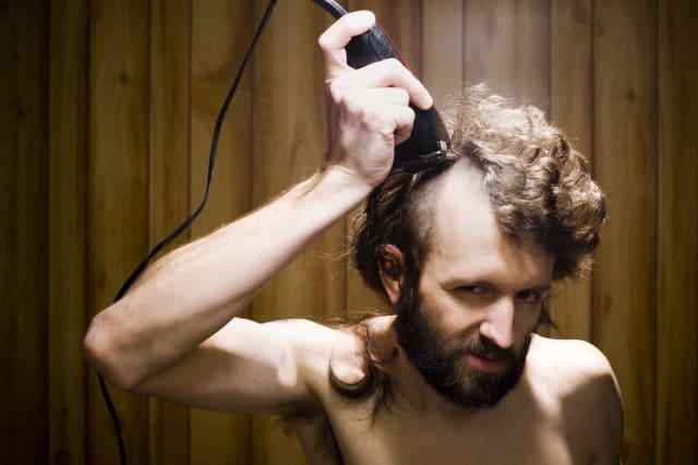 Man shaving head with electric razor