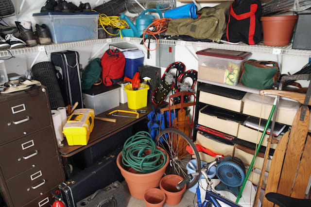 BP2BD7 Big mess in an over stuffed suburban garage. garage; junk; mess; home; interior; bike; sled; snowshoes; tools; boxes; she
