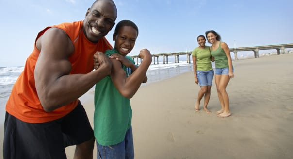 Father and Son Flexing Muscles on Beach