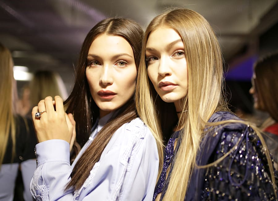 The sisters, at a fashion show in Milan, both look striking wioth super straight