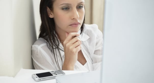 Woman deep in thought while looking at laptop