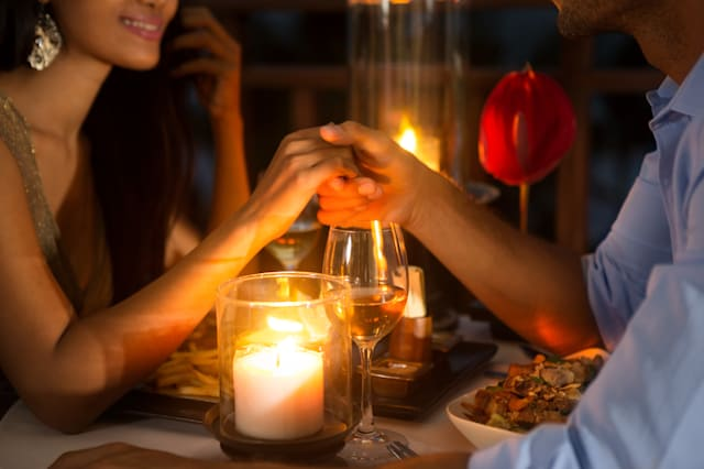 Romantic couple holding hands together over candlelight during romantic dinner