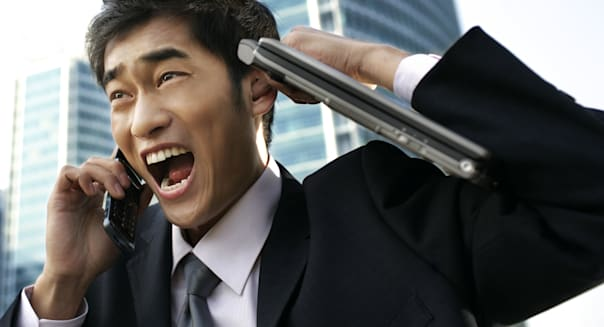 Business man yelling to mobile phone outdoors