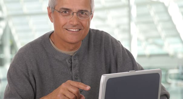 Middle aged man sitting and pointing at laptop computer in modern office setting. Man is smiling and casually dressed looking at