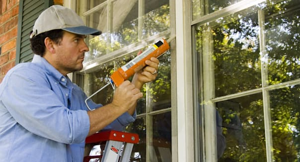 Man on ladder caulking outside window