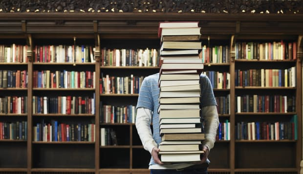 Young man carrying stack of books in university library