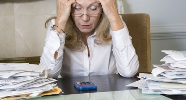 Frustrated woman paying bills.
