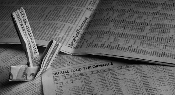 B4MHX8 Mutual Funds are displayed on a newspaper with a five dollar bill in the shape of an arrow pointing towards the mutual fu