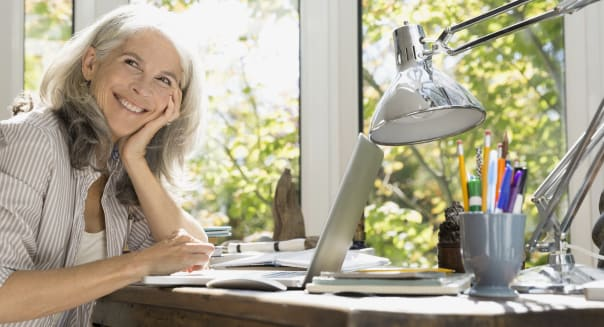 Smiling senior woman at laptop in home office